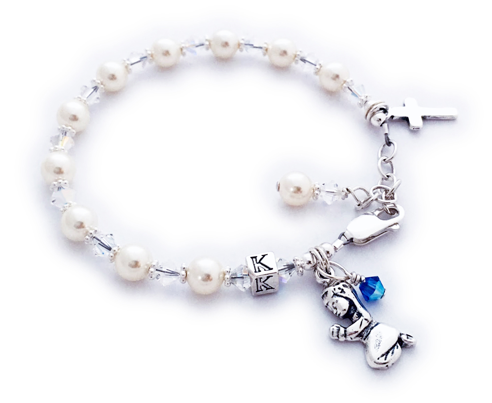JBL-MB-7 Confirmation or First Communion Bracelet (Shown with an add-on birthstone crystal dangle charm) Clear Swarovski Crystals and Pearls with a Praying Girl charm and Simple Cross charm come on this beautiful First Communion or Confirmation bracelet. They picked the initial K during the ordering process and added a September Birthstone Crystal dangle. The sterling silver lobster clasp with an extension comes with this bracelet so it will grow with the little girl.